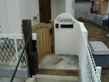 可愛いアイアン調表札を付けた白塗りの門まわり 門袖は丸く取って可愛らしい印象