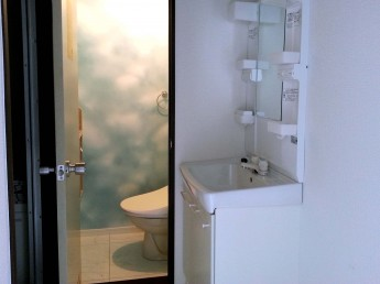 雲の柄の明るい壁紙を貼ったトイレ