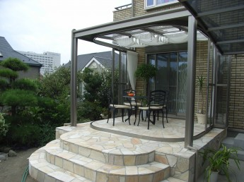ガーデンルームを付けたテラス 丸く角を取った階段で柔らかな印象