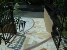 重厚感あふれる門扉の先に広がる自然石アプローチ