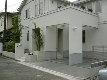 白い建物に植栽の緑が映える門構え。