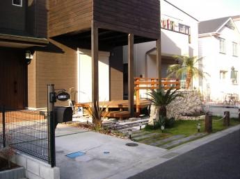 リゾート風の外構のアプローチは枕木と芝、白い化粧砂利を
