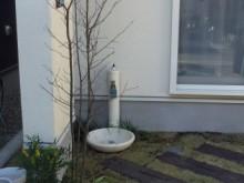 白い建物にマッチした白い立水栓 枕木と芝の水まわりもナチュラルな雰囲気が出ています