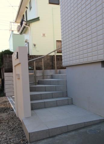 門袖の裏には玄関へつながる階段。高さのあるアプローチの為手すりを付けています。
