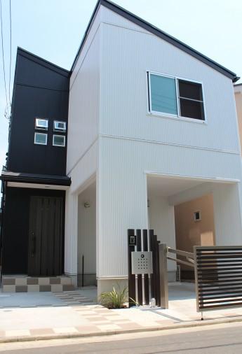 片流れ屋根のかっこいい建物に濃いめカラーを使った角柱でオリジナルの門柱