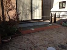 デッキの床下は駐車場の床材とつなげてレンガとコンクリートで