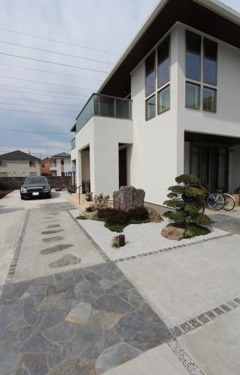 玄関へと続く、ピンコロ+洗出し+自然石のアプローチ。和風小庭を添えて…