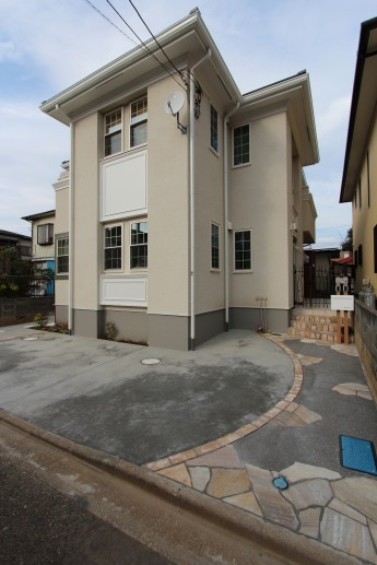 オープンな駐車場にはレンガのカーブラインと自然石の乱貼りをポイントで使用