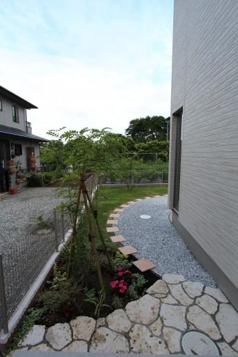 門まわりを抜けると、お庭につながるタイルのアプローチが円形に敷かれています