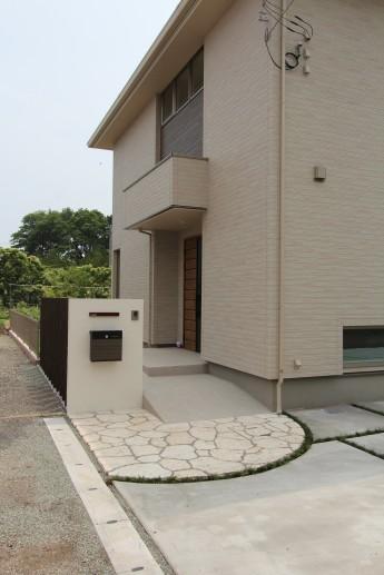 琉球石灰岩のアプローチに白い門袖、木調ポストや表札が玄関周りを華やかに