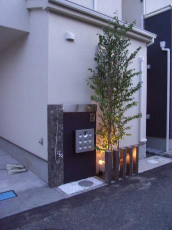 水栓の付いた個性的な門袖にスポットライトで樹木を照らす
